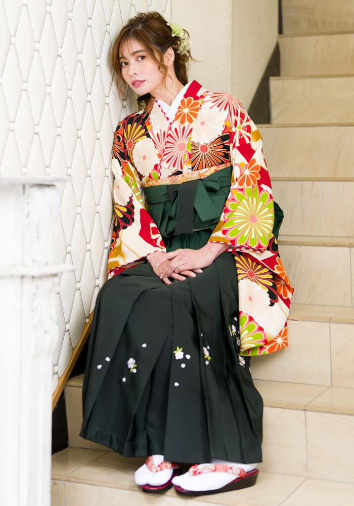 【着物】白赤に大菊+【袴】フカミドリボカシシシュウの座ってるコーデ
