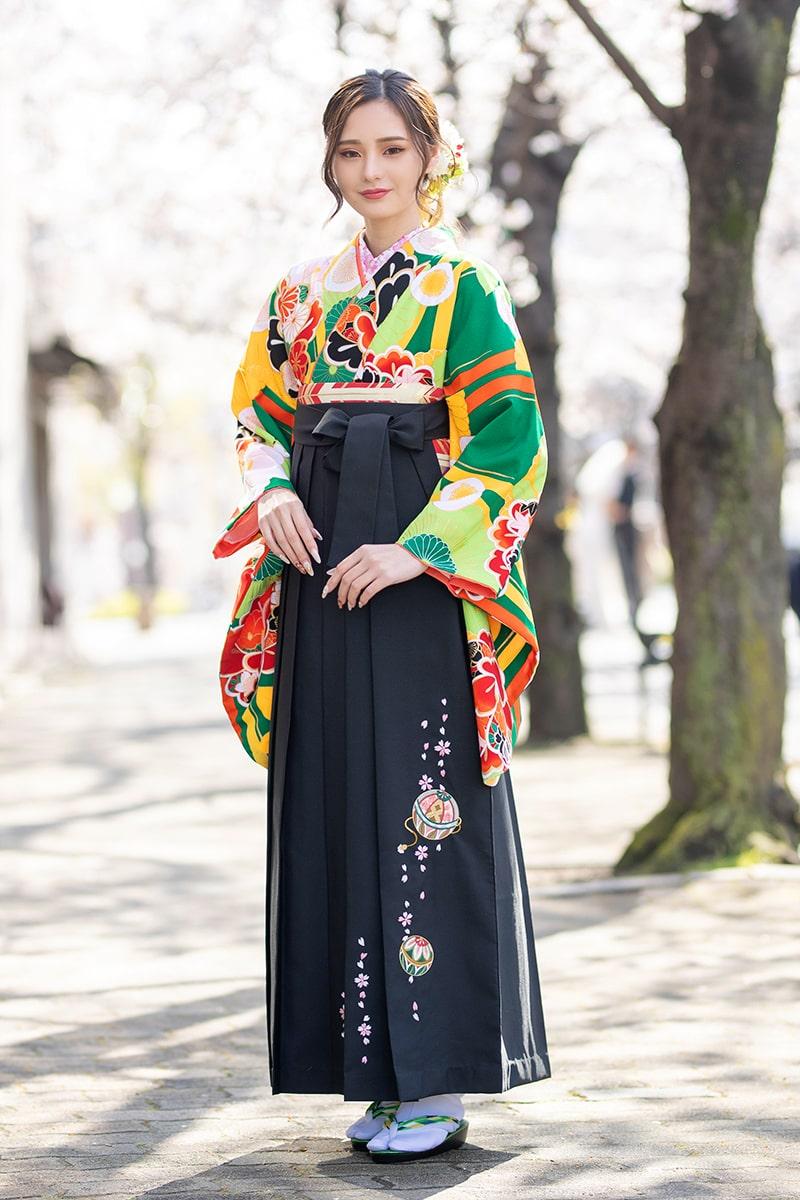 着物:緑に菊椿/袴:クロ手まりシシュウ。緑地に、淡く咲き誇るようにあしらわれた花柄が落ち着いた大人の雰囲気に。