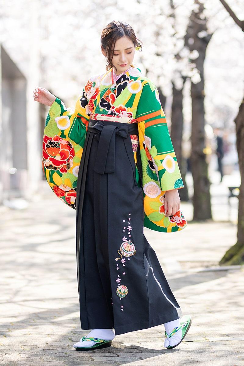 着物:緑に菊椿/袴:クロ手まりシシュウ。手毬と桜の刺繍が紺地の袴をにピッタリ。 チョット大人びた雰囲気を楽しみたい方におススメです。