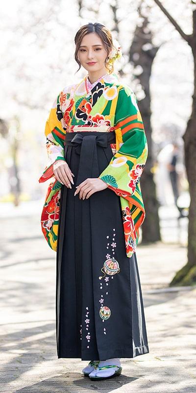 着物:緑に菊椿/袴:クロ手まりシシュウ。緑地に菊や椿の花柄をあしらった着物[BBB464]に、紺色の手毬柄の袴[KUT082]の組み合わせ。