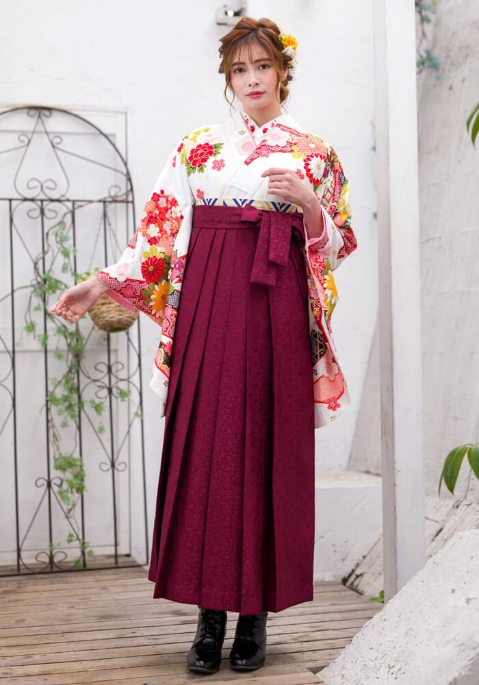卒業式で人気の白地の着物と赤い桜小紋の袴。