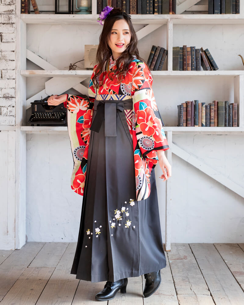赤地の着物に黒い袴を合わせたクールで華やかなコーディネートの女性。