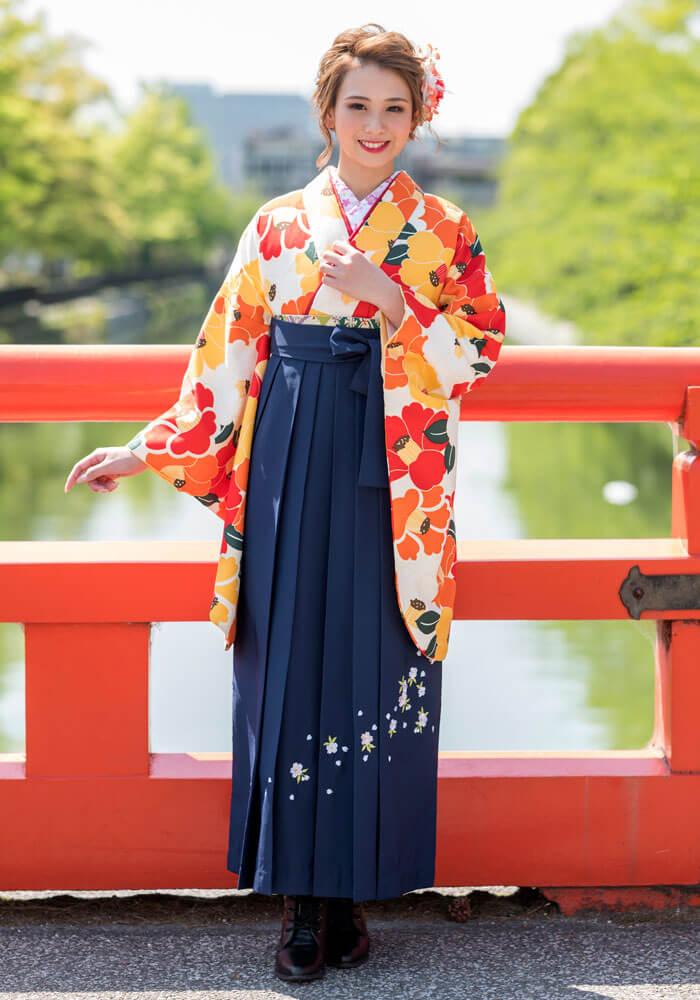 華やかなオレンジの着物を、クールな紺の袴で締めたオシャレなレンタル袴コーディネート。