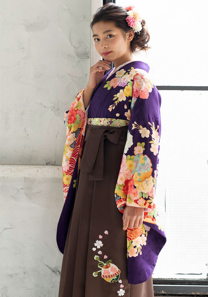 紫の古典柄着物に茶色の袴を合わせてレトロに着こなした袴コーデ