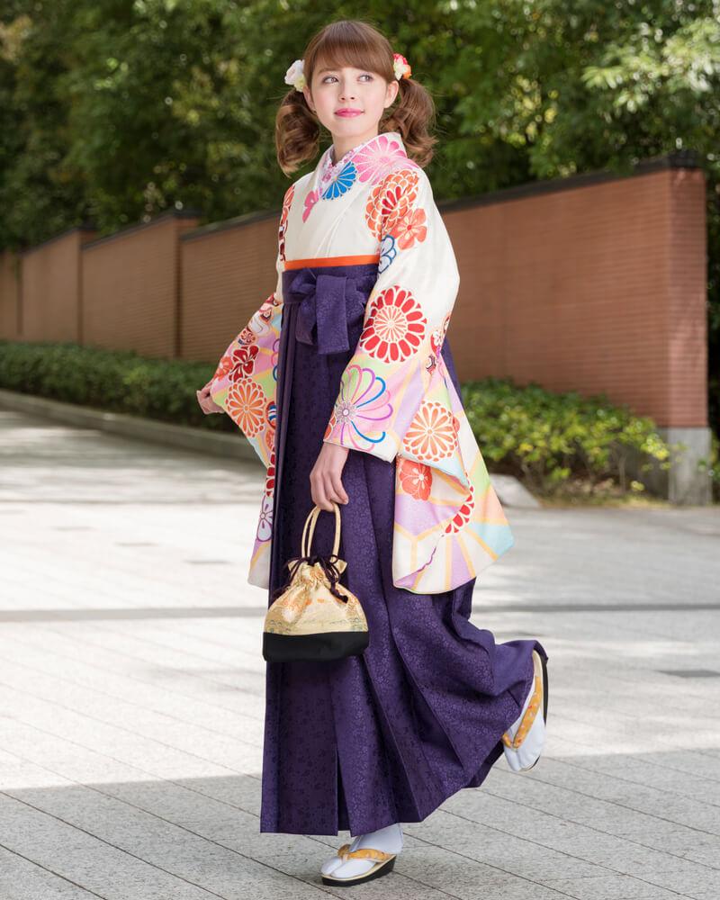 クリーム地に矢車柄の着物[DDD869]と紫色の袴[MSK093]を組み合わせた卒業袴コーデ。淡い優しい印象を与えるクリーム地にパステルカラーの矢車柄が華やか。